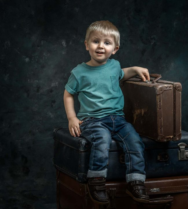 Young boy sat on suitcases